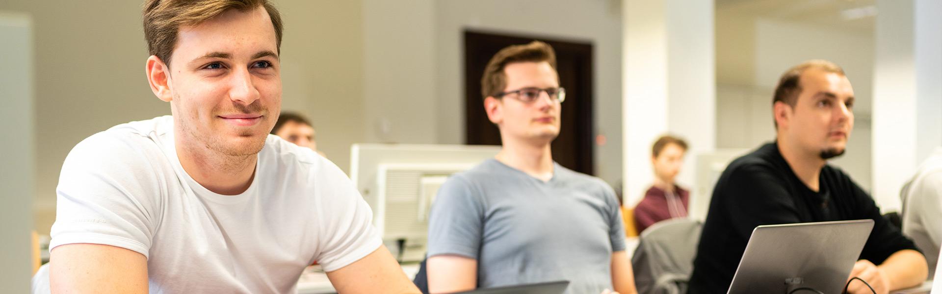 Informatik Master-Studium in Görlitz: Im Fokus ist ein junger Mann, der scheinbar auf einen Bildschirm schaut.
