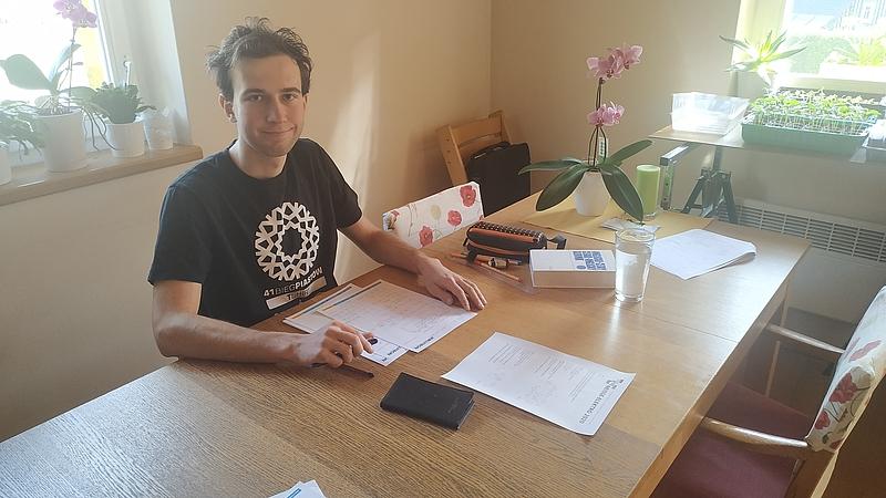 Männlicher Teilnehmer an Esstisch mit Zettel und Stift