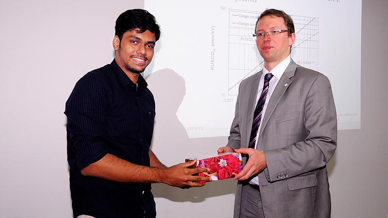 Indischer Student bekommt Präsent von Professor Kornhuber überreicht