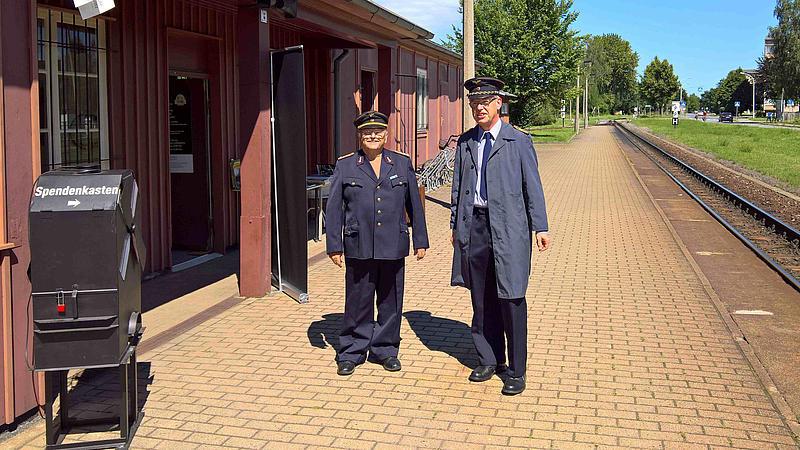 Lehrbeauftragter Hans-Günter Krüger und Laboringenieur Volker Brade vor dem Besucheransturm  in Dienstkleidung der Deutschen Reichsbahn vor dem Bahnhof Zittau Süd